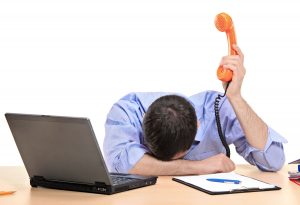 Exhausted businessman holding a telephone tube in his office against white background